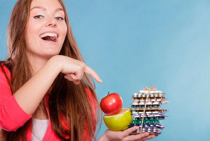 Девушка держит в руках разные витамин